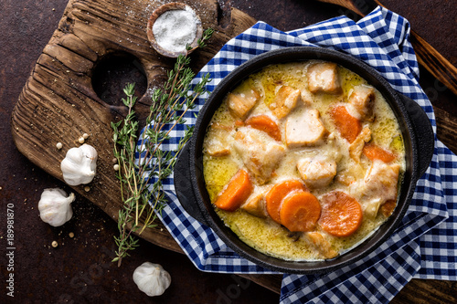 Fotografie, Obraz  Meat stew, chicken fillet in sauce with carrot in a cast iron pot, top view