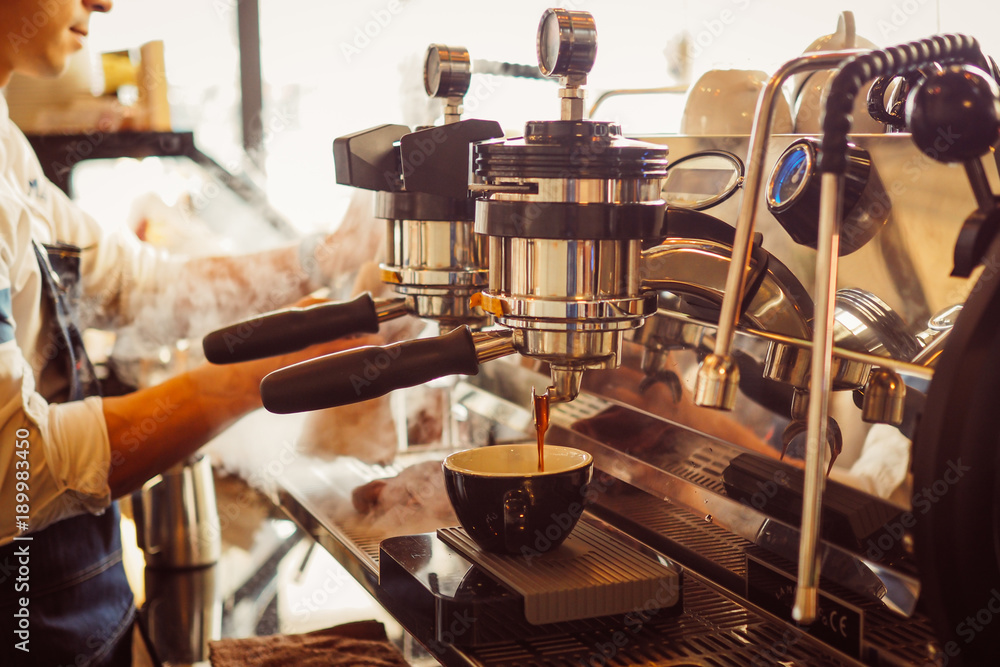 Fototapeta barista make coffee latte art with coffee espresso machine in coffee shop cafe in vintage color tone