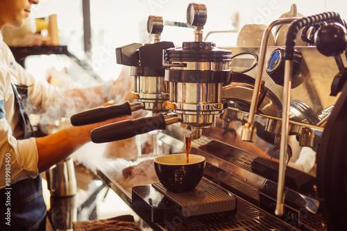 Fototapeta Barista robiący kawę latte za pomocą ekspresu do kawy w kawiarni na ścianę