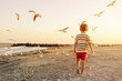 Kid running at the beach by background of orange sunset and flying seagulls