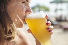 Woman Drinking Beer With A Glass On The Beach
