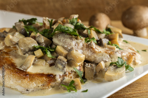 Pork sirloin with white sauce made from sour cream and mushrooms with parsley