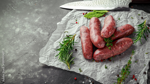 Cuadros en Lienzo Freshly made raw breed butchers sausages in skins with herbs on crumpled paper