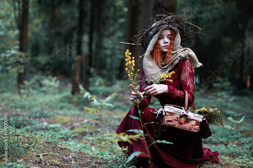 Obraz na plátně The red-haired witch holds a ritual with a crystal ball