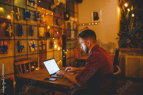 man with beard businessman working behind laptop in coffee shop in evening. interior decorated with Christmas decor, light bulbs are shining, hands on keyboard typing text. The concept small business