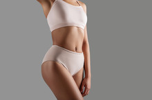 Close Up Of Woman In Underclothes Demonstrating Her Well Groomed Thin Figure. Copy Space On Right Side. Isolated On Background