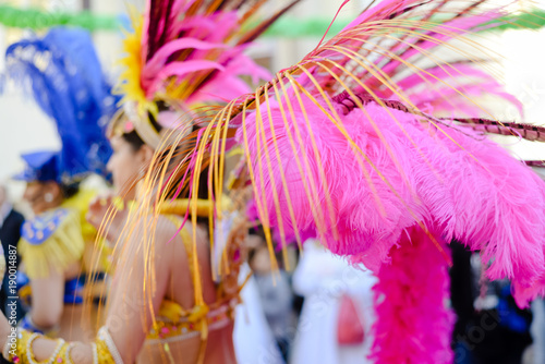 Blurry joyful female performers at the carnival party parade on outdoors background. Back side view having fun hot festive sexual glamour show with traditional sensual beauty feathers and clothing