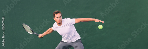 Tennis game man athlete hitting ball during match point on indoors tennis court at fitness health club. Panorama banner on green background.