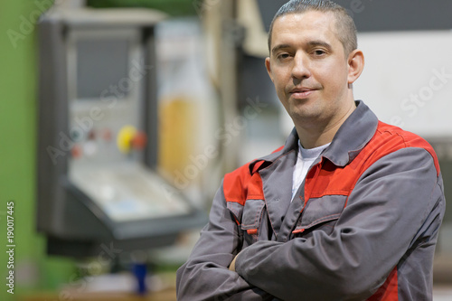 Photo Service man worker with folded arms at factory workshop background