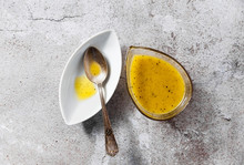 Dressing For Salad From Olive Oil And Lemon In A Serving Dish And A Silver Spoon On A Stone Table