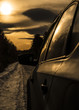 car on the road close up, silhouette on sunset background