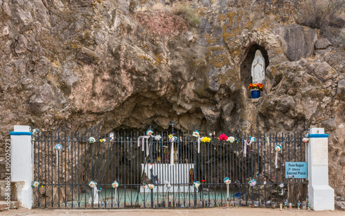 Photo Tucson, Arizona, USA - January 9, 2018: Grotto in rocks with statues of Mary and Bernadette outside historic San Xavier Del Bac Mission