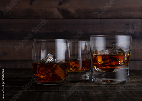 Foto op Canvas Alcohol Glasses of whiskey with ice cubes on wooden table