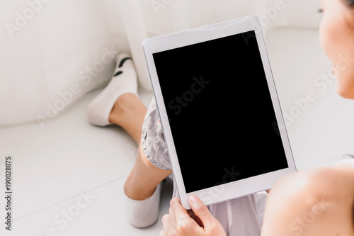 Woman using digital tablet computer in bedroom