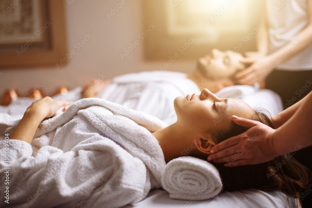 Fototapeta Young couple receiving head massage at beauty spa