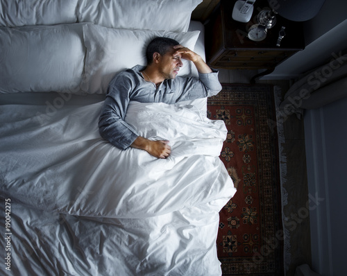 Man on bed with a headache Canvas Print