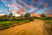 Rural Australian Landscape With Colorful Clouds Ans Dirty Gravel Road In Outback Of Australia At Sunrise/sunset