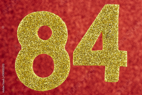 Fotografia  Number eighty-four yellow color over a red background