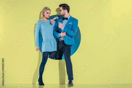 attractive stylish couple stepping through aperture on yellow Poster