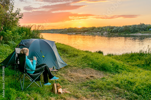 Poster de jardin Camping Young woman in camping with a tourist tent on the river bank. Russia.