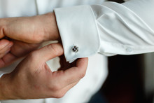 A Man Wears Buttons Of Cufflinks On The Sleeves Of The White Shirt. Businessman Getting Dressed By The Window.