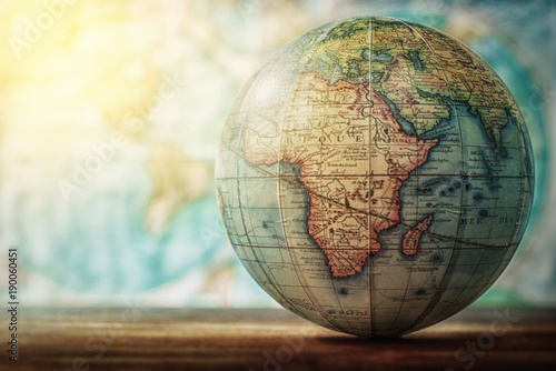 Photo Stands World Map Adventure stories background. Old globe on map background. Selective focus.