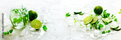 Poster Cuisine Homemade lime lemonade with cucumber, rosemary and ice, white background. Cold beverage, detox water. Copyspace. Banner
