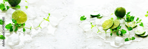 Homemade lime lemonade with cucumber, rosemary and ice, white background. Cold beverage, detox water. Copyspace. Banner