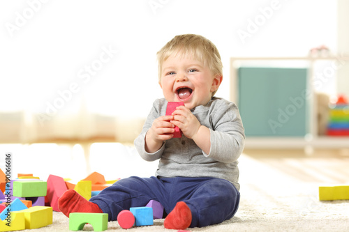 Fotografie, Obraz  Baby laughing and playing with toys on a carpet