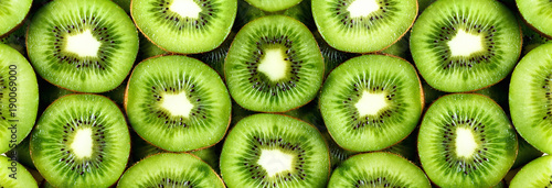 Photo Stands Fruits Fresh organic kiwi fruit sliced. Food frame with copy space for your text. Banner. Green kiwi circles background