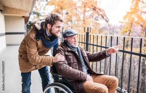 Fotografía  Senior father in wheelchair and young son on a walk.