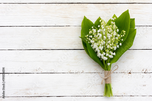 Poster Muguet de mai a bouquet of flowers fragrant lilies of the valley on white wooden background with copy space. mock up for text, for phrases, for lettering