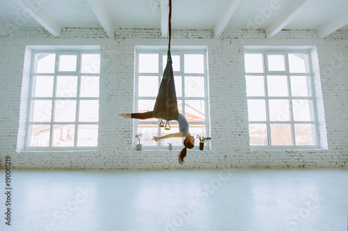 Photo Young woman doing fly yoga exercise and stretching in front of windows on white background in loft interior studio