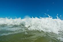 Foam On A Crest Of A Sea Wave Against A Blue Sky. Closeup