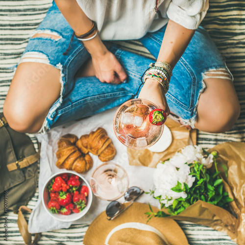 Keuken foto achterwand French style romantic picnic setting. Woman in jeans with glass of wine, strawberries, croissants, brie cheese, sunglasses, peony flowers on blanket, top view, square crop. Outdoor gathering concept