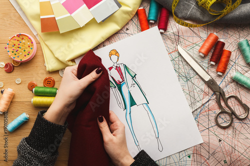 Valokuva Female fashion designer working with fabric sample and drawn illustration