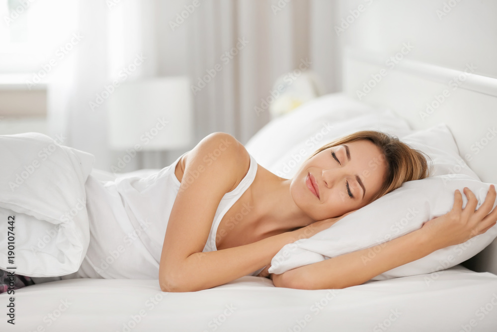 Fototapeta Young woman sleeping on white pillow in bed
