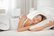 canvas print picture - Young woman sleeping on white pillow in bed