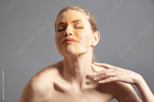 Young woman with honey on her face against grey background Canvas Print