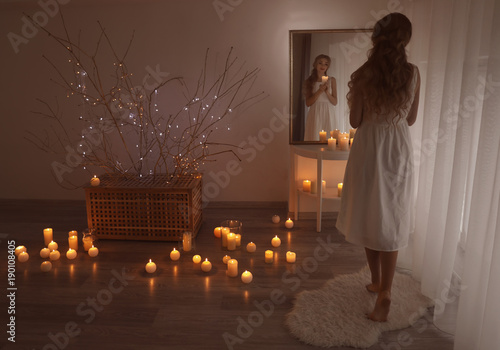 Foto op Plexiglas Wand Beautiful young woman holding candle and looking in mirror at home