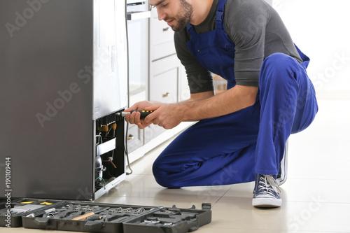 Pinturas sobre lienzo  Male technician repairing refrigerator indoors