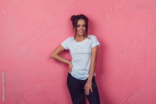 Obraz Attractive woman in a white t-shirt stands on a pink background. Mock-up. - fototapety do salonu