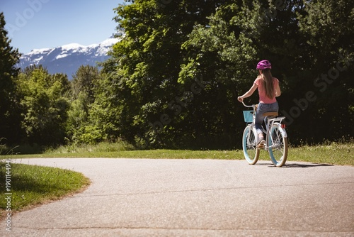 Girl wearing safety helmet riding bicycle on road on a sunny day