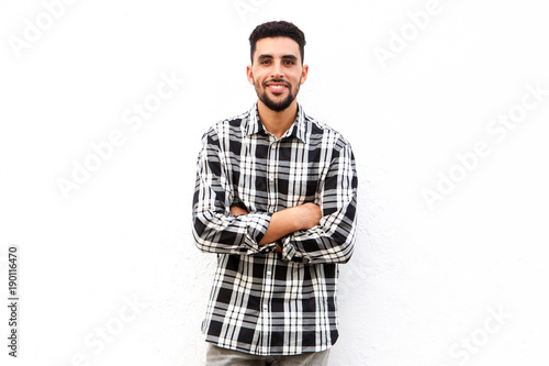 Fotografie, Obraz  North African man smiling against white background with arms crossed
