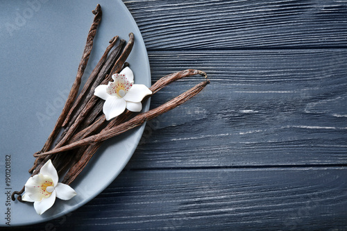 Plate with vanilla sticks and flowers on wooden background
