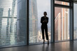 Business woman holding a tablet and standing in a modern office. Panoramic windows background.