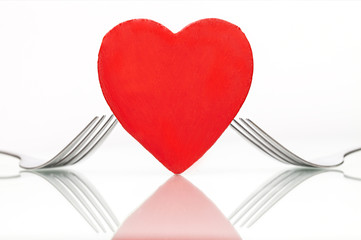 Heart with forks on table