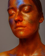 Glowing neon makeup with dramatic look in his eyes. Creative body art on the theme of space and stars. Amazing close-up portrait glow in the dark makeup.