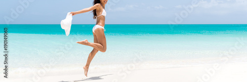 Fototapeta Happy beach body woman jumping of joy with sun hat on caribbean travel vacation. Slim legs sexy bikini girl sun tanning feeling free. Banner panorama with copy space on blue ocean background obraz
