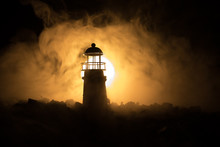 Lighthouse With Light Beam At Night With Fog.